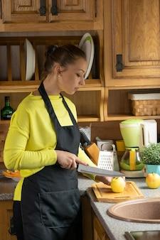 美しい料理人は木製のまな板にリンゴをスライスします