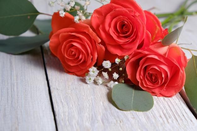 白い木製のテーブルの上の美しい珊瑚のバラとユーカリ。