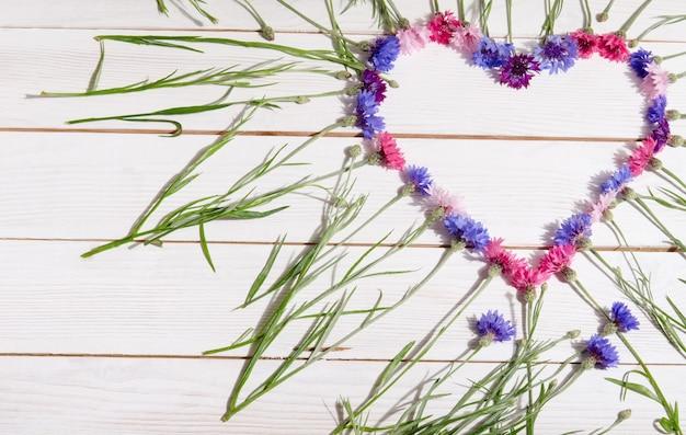 나무 테이블에 심장의 모양에 아름 다운 cornflowers