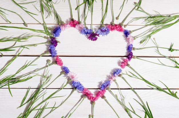 Beautiful cornflowers in shape of heart on wooden background