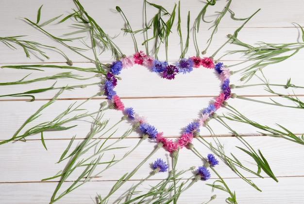 Beautiful cornflowers in shape of heart on wooden surface