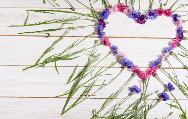 Beautiful cornflowers in shape of heart on wooden table