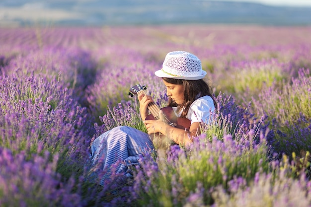 Beautiful country girl in a hat resting in a field with lavender and playing on the ukulele