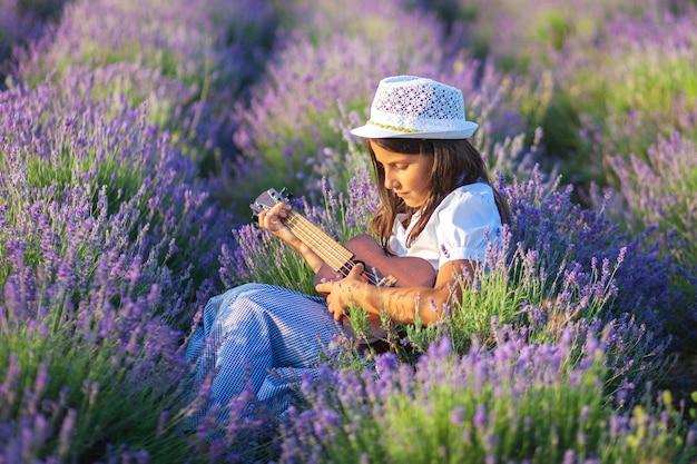 帽子の美しいカントリーガールはラベンダー畑に座っている間小さなギターを弾く