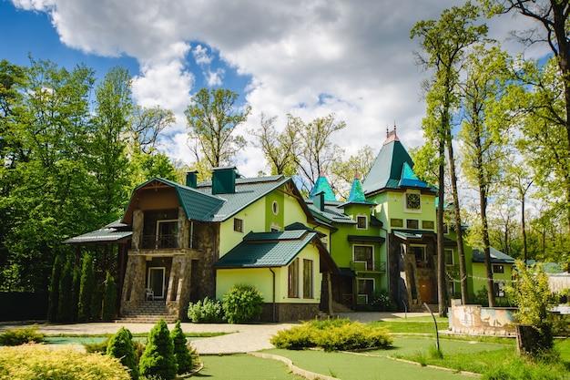 숲에서 녹색 톤의 아름다운 컨트리 빌라.