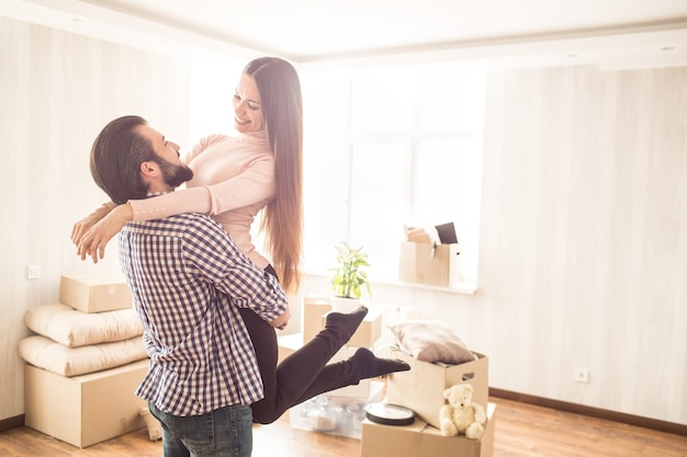 Beautiful couple are standing in a bright room with unpacked boxes