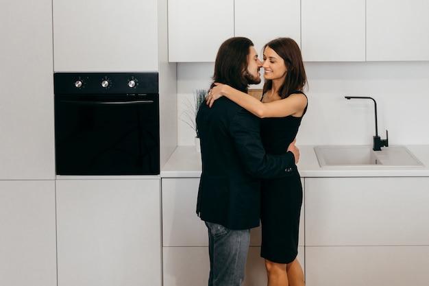 그들의 이마와 손을 잡고 서로 만지고 부엌에서 집에서 아름 다운 커플. 고품질 사진