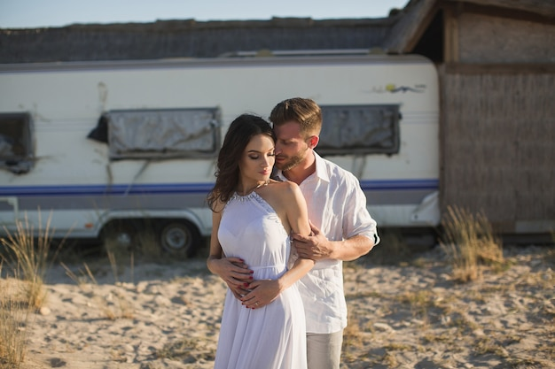 Beautiful couple on the beach, on the background of the trailer van.