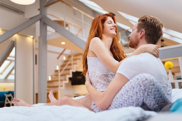 ベッドでロマンチックで情熱的な美しいカップル