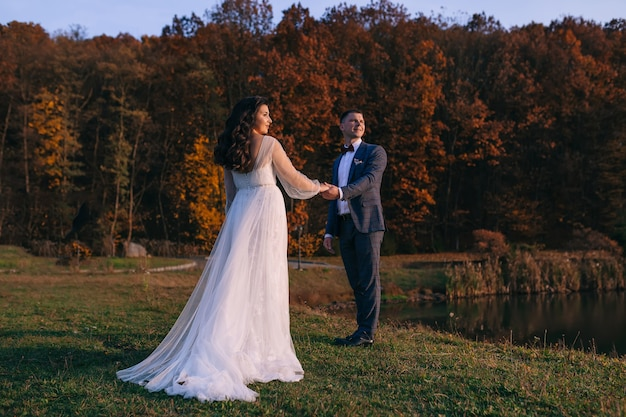 A beautiful couple of the bride and groom hold hands and walk surrounded by beautiful nature