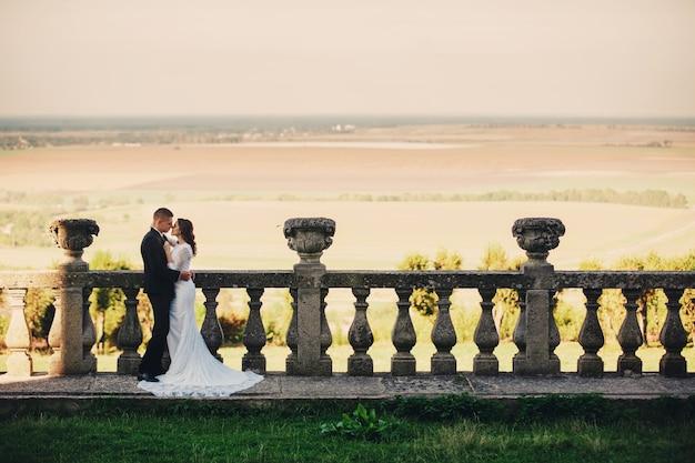 Beautiful couple, bride and groom posing on balcony