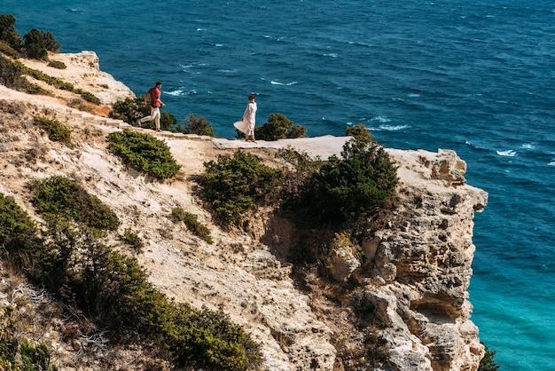海沿いの美しいカップル。ハネムーン旅行。恋人たちは海のそばでデートします。恋をしているカップルは海で休暇を過ごします。結婚式の旅行。休日のロマンス。海のツアー。コピースペース