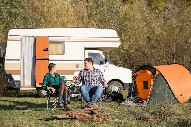 그들의 복고풍 캠핑카 밴으로 산에 있는 캠프장에서 함께 캠핑하는 아름다운 커플. 캠핑 텐트.