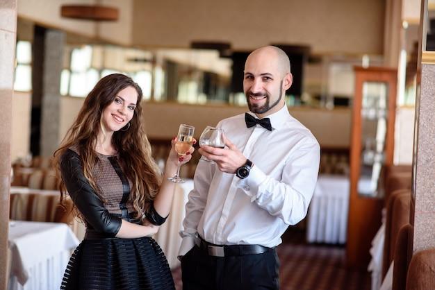 Красивая пара празднует и пьет шампанское в ресторане