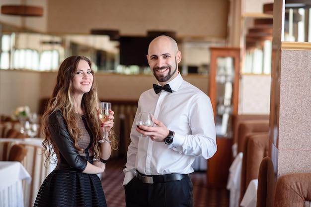 Красивая пара празднует и пьет шампанское в ресторане.