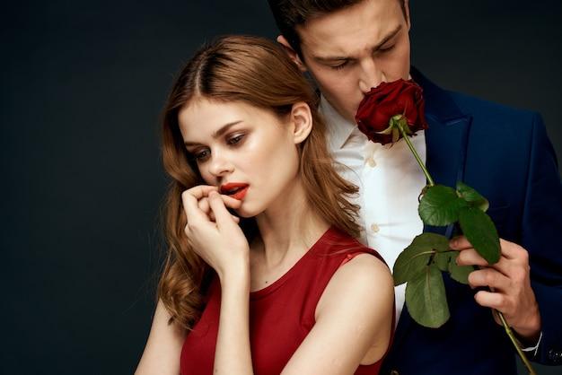 Очарование красивой пары, обнимающей и держащей розу на черном фоне