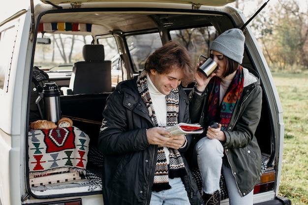 ロードトリップしながら地図をチェックする美しいカップル