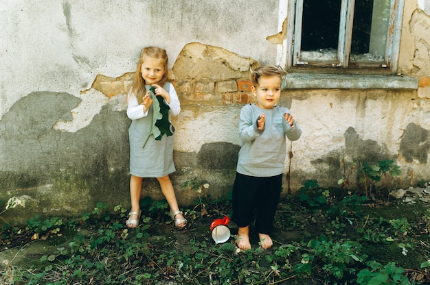 A beautiful couple of children in gray suits are playing against the background of the wall