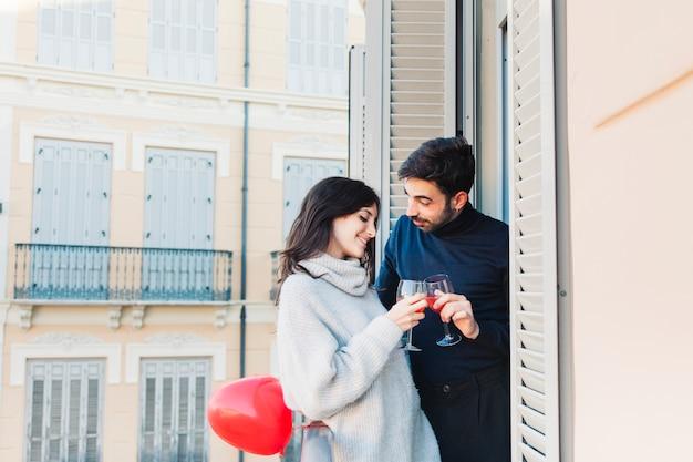 美しいカップル、バルコニーで眼鏡をかがめる