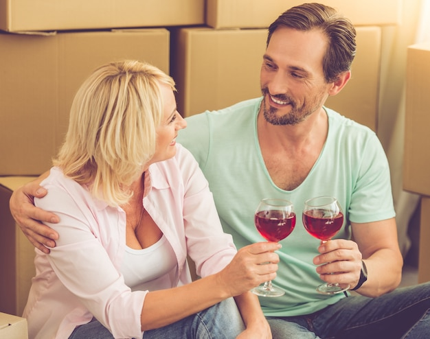 Beautiful couple in clothes are clanging glasses of wine
