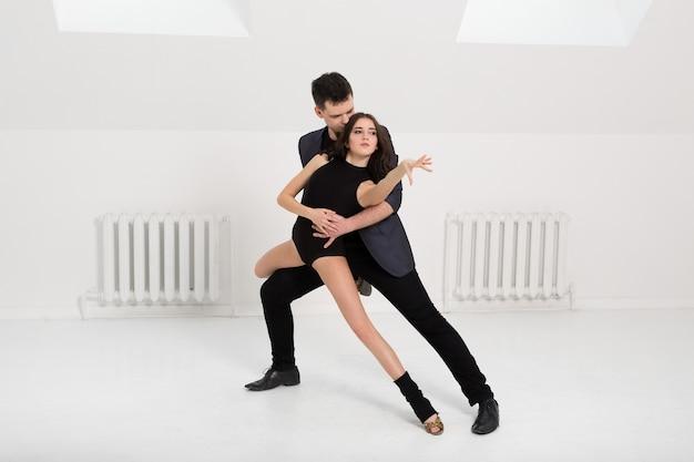 スタジオで白い背景にバチャタを踊る美しいカップル