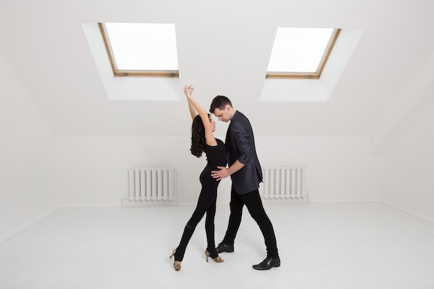 Красивая пара танцует бачату на белом фоне в студии