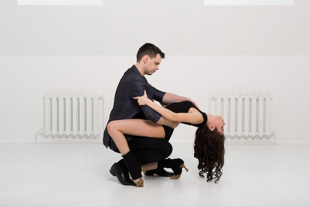 Beautiful couple dancing bachata on white room