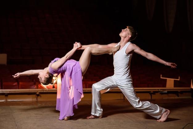 暗いステージで踊る美しいカップル。