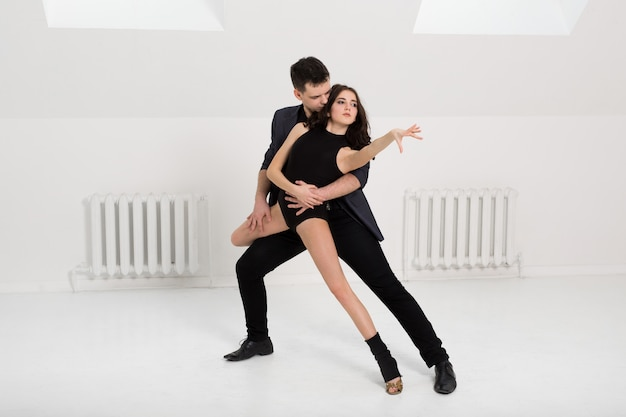 Beautiful couple dancing on white background in studio
