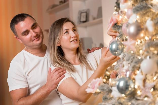 Belle coppie che decorano l'albero di natale