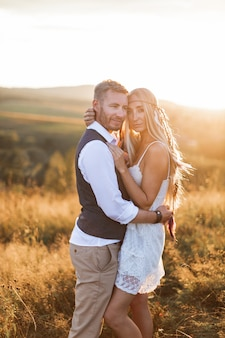 Beautiful couple dressed in boho style embracing each other in the sunny summer field
