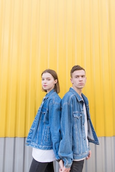 Beautiful couple dressed in denim jackets stands on background of yellow wall.