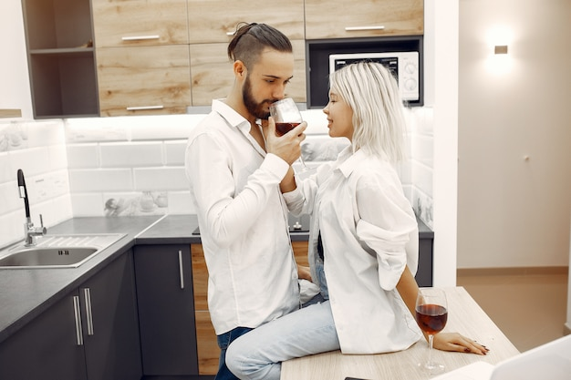 Beautiful couple drink red wine in the kitchen