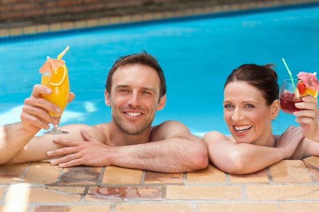 スイミングプールで美しいカップルの飲み物のカクテル