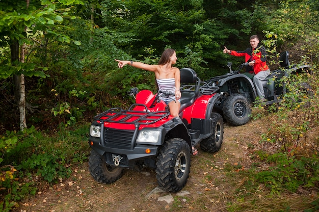 Beautiful couple driving four-wheelers atv and looking at each other.