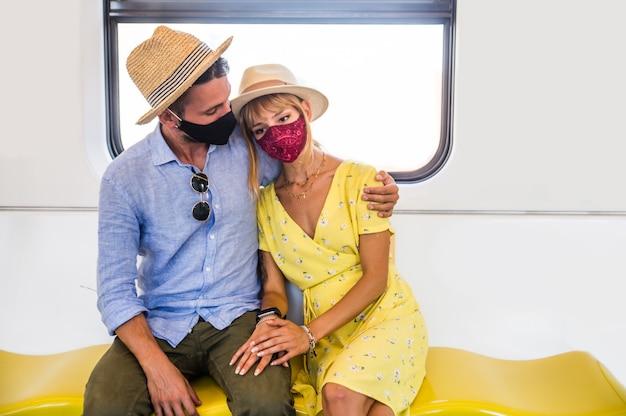 Covid-19 대유행 동안 지하철 마차에서 운전하는 아름다운 커플