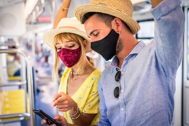 Красивая пара едет в вагоне метро во время пандемии covid19