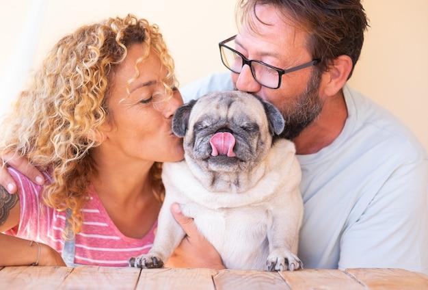 彼らの古いパグ犬を抱きしめてキスする美しいカップル。素敵な家族と親友のコンセプト