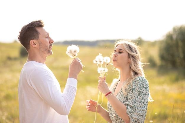 Beautiful couple enjoying nature blowing on dandelions, enjoying each other's company, lifestyle