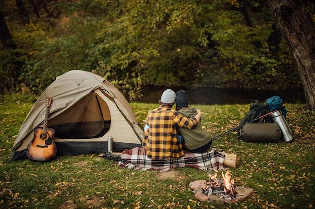 Beautiful couple enjoying nature near tent sitting on log
