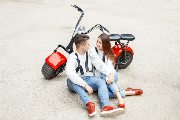 Beautiful couple in fashionable denim clothes rest near a red electric bike on white sand