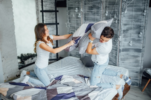 Beautiful couple fight with pillows in their room.