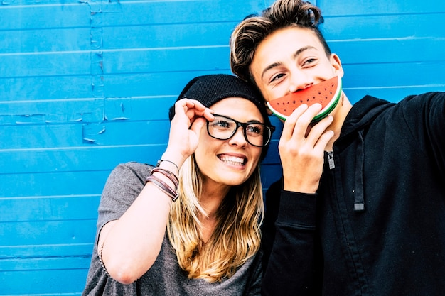 Beautiful couple of friends playing and enjoy together with blue background looking and smiling at the camera - girl smiling with a watermelon on her mouth and guy with glasses - girl with blue eyes