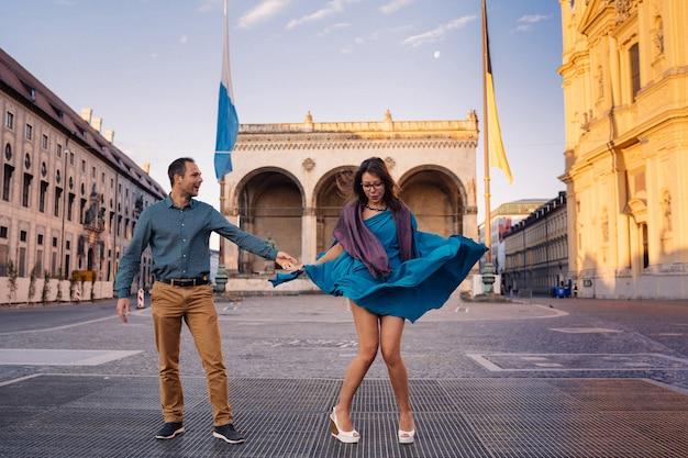 美しいカップルは旧市街でデートし、女の子は片方の手で彼女の飛行服を止めようとし、もう片方の手で彼氏の手を握っていました。