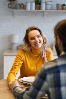 Beautiful couple having a conversation while looking at each other sitting at the table in a kitchen