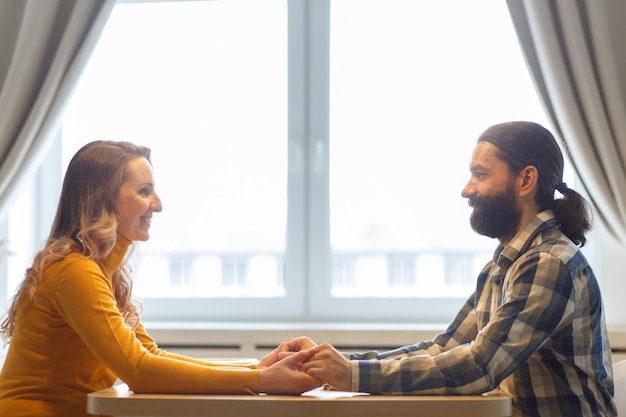 Beautiful couple having a conversation while looking at each other over a window background in a bright room
