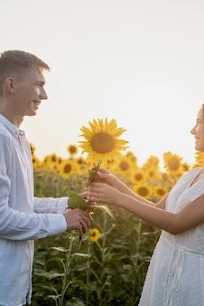 Beautiful couple having fun in sunflowers fields, man giving girlfriend a sunflower