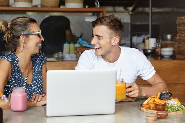 Beautiful couple having lively conversation sitting at table with laptop and food in cozy cafeteria interior