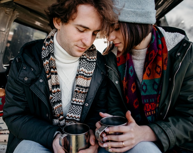 Beautiful couple holding cups of coffee in a van
