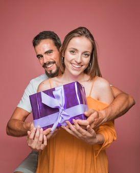 Beautiful couple holding purple gift box against colored background